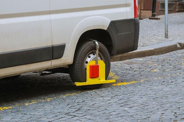 Koło samochodu jest zablokowane z powodu naruszenia zasad parkowania.