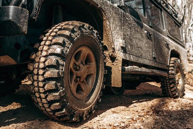 Koło samochodu terenowego w błotnistym lesie drogowym
