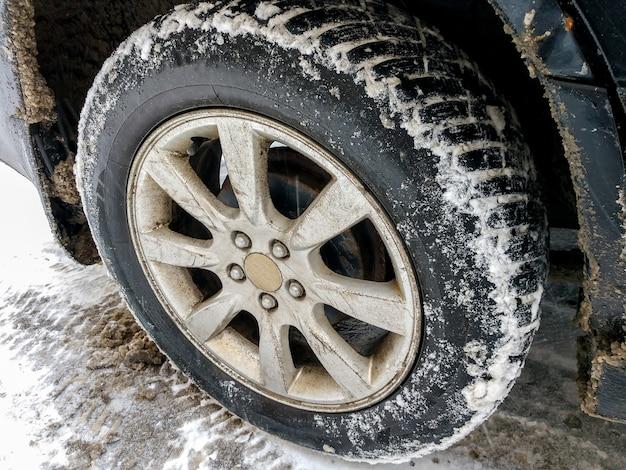 Koło samochodu z przyklejonym śniegiem czarny samochód stoi na zaśnieżonej drodze
