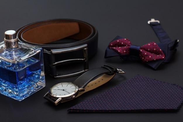 Kolonia dla mężczyzn, skórzany pasek z metalową sprzączką, zegarek z czarnym skórzanym paskiem, muszka i chusteczka na czarnym tle. akcesoria dla mężczyzn.