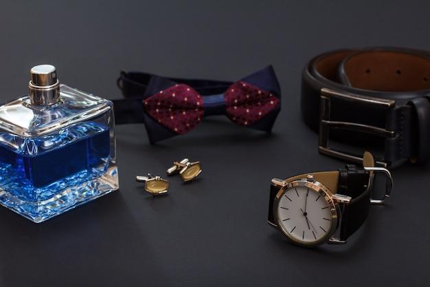 Kolonia dla mężczyzn, spinki do mankietów, muszka, zegarek z czarnym skórzanym paskiem i skórzanym paskiem z metalową sprzączką na czarnym tle. akcesoria dla mężczyzn.