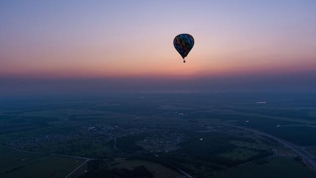 Kolor balonu na ogrzane powietrze w tle nieba i wschodu słońca w czasie porannym