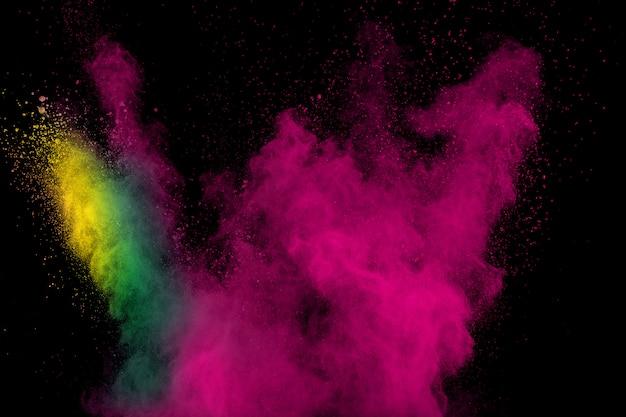 Kolor chmura eksplozji proszku na czarnym tle. bryzgające cząsteczki pyłu.