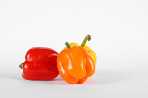 Kolor czerwony i pomarańczowy papryki na białym tle