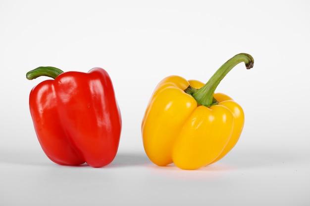 Kolor czerwony i żółty papryki na białym tle