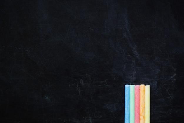 Kolor pisze kredą na czarnej tablicy kredą