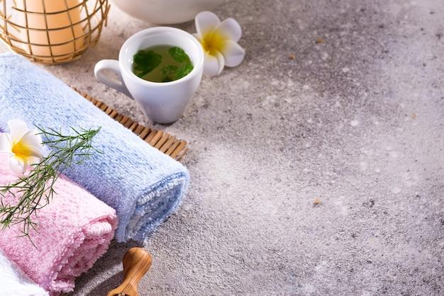 Kolor ręczników z kwiatkiem, łyżką soli, na bambusowej macie, kąpieli spa i zielonej herbaty na kamiennym stole, copyspace