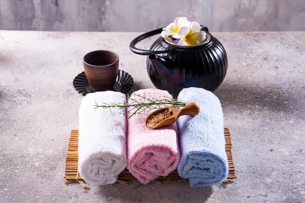 Kolor ręczników z zielonymi liśćmi, łyżką soli i herbaty detoksykacyjnej na bambusowej macie i kamiennym stole