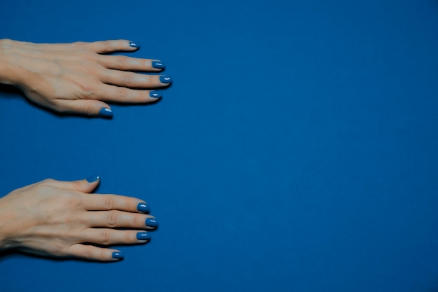 Kolor roku 2020. piękne, wypielęgnowane paznokcie kobiety z klasycznym niebieskim lakierem do paznokci