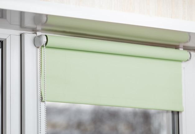 Kolor rolety zaciemniające na białym plastikowym oknie. okiennice na plastikowym oknie.