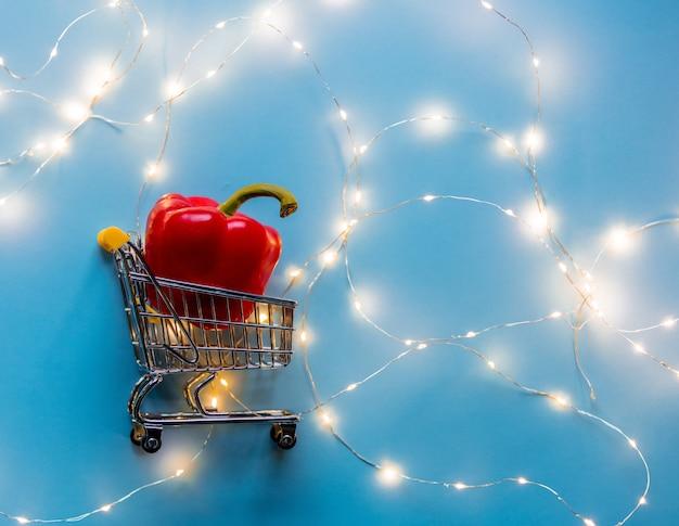 Kolor słodkiej papryki w wózku supermarketu z bajkowymi światłami na niebieskim tle