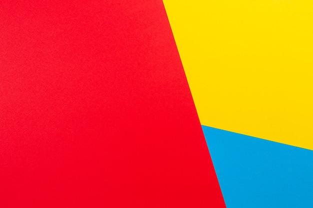 Kolor tła płaskiej kompozycji geometrii papiery z żółtymi czerwonymi i niebieskimi odcieniami