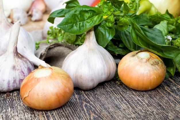Kolor zielony czosnku i bazylii wraz z cebulą podczas gotowania, stół kuchenny podczas gotowania potraw, zbliżenie