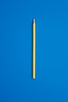 Kolor żółty barwiony ołówek odizolowywający na błękita stole