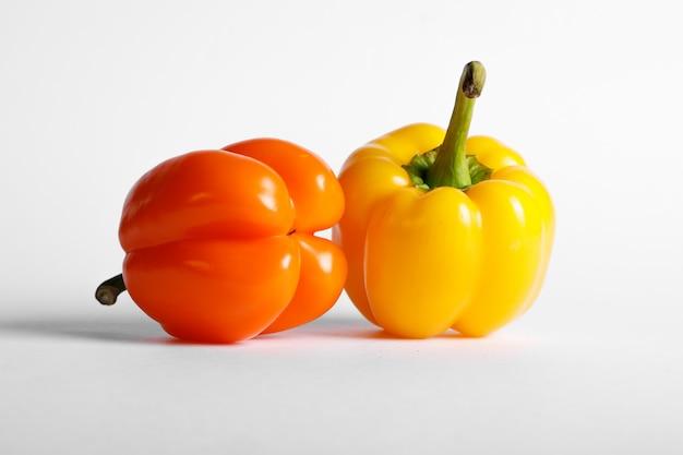 Kolor żółty i pomarańczowy pieprze na bielu