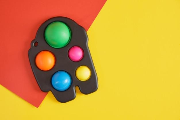 Kolorowa antystresowa zabawka sensoryczna fidget push pop lub prosty dołek na żółtym i czerwonym tle kopia przestrzeń widok z góry
