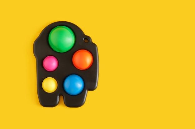 Kolorowa antystresowa zabawka sensoryczna fidget push pop lub prosty dołek na żółtym tle kopiuj przestrzeń widok z góry