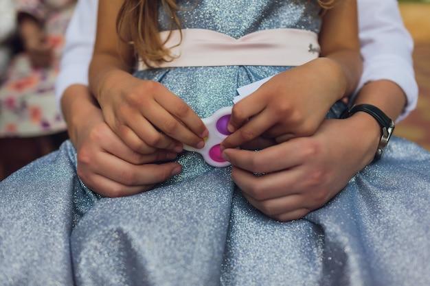 Kolorowa antystresowa zabawka sensoryczna fidget push pop w rękach dzieci