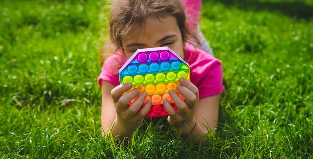 Kolorowa antystresowa zabawka sensoryczna typu fidget push pop w dziecięcych dłoniach. selektywna ostrość. natura.