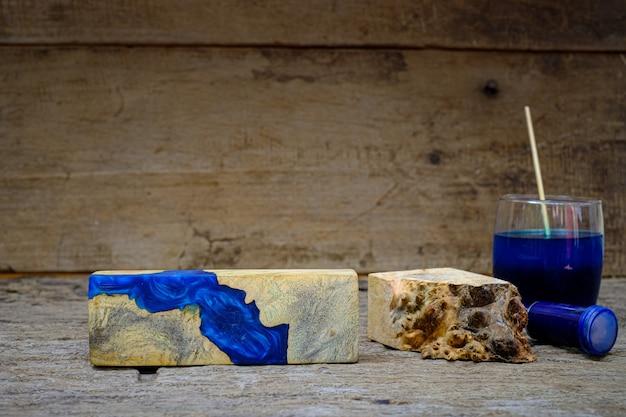 Kolorowa butelka zrębków drewnianych i żywica epoksydowa do odlewania drewna na starym drewnianym stole w tle