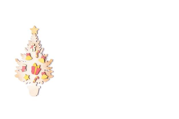 Kolorowa choinka z dekoracjami sylwestrowymi na białym tle. czerwone pudełko, cukierki, złote gwiazdki na karcie świątecznej. płaski układanie, widok z góry