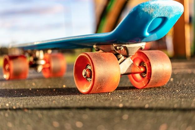 Kolorowa deskorolka z pomarańczowymi kołami z bliska na placu zabaw.