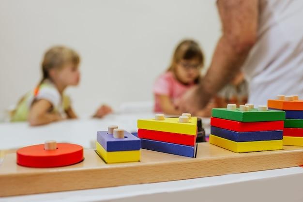 Kolorowa drewniana zabawka na białym biurku przeciwko studiującym dzieciom