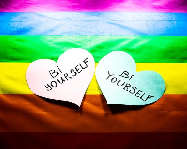 Kolorowa flaga społeczności lgbt. bi siebie znaki na sercach na tle tęczy. problemy lesbijek, gejów i osób biseksualnych. legalizacja małżeństw dla par o orientacji homoseksualnej.