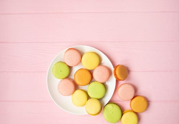 Kolorowa francuska lub włoska macarons sterta na bielu talerzu stawia dalej różowego drewno stół z kopii przestrzenią dla tła. deser podawany z popołudniową herbatą lub przerwą na kawę.