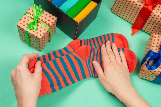 Kolorowa kolekcja bawełnianych skarpet jako prezent w rękach kobiety.