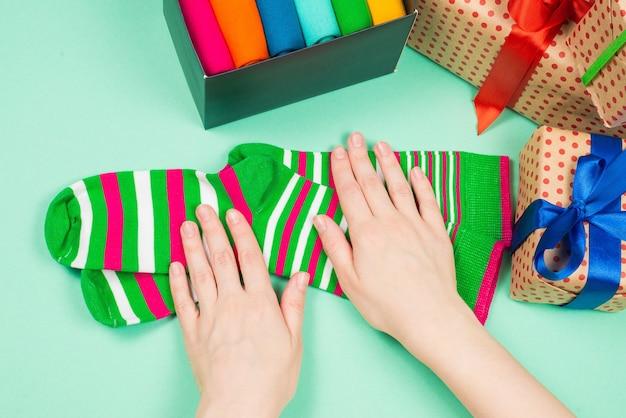 Kolorowa kolekcja bawełnianych skarpetek na prezent w rękach kobiety. prezent.