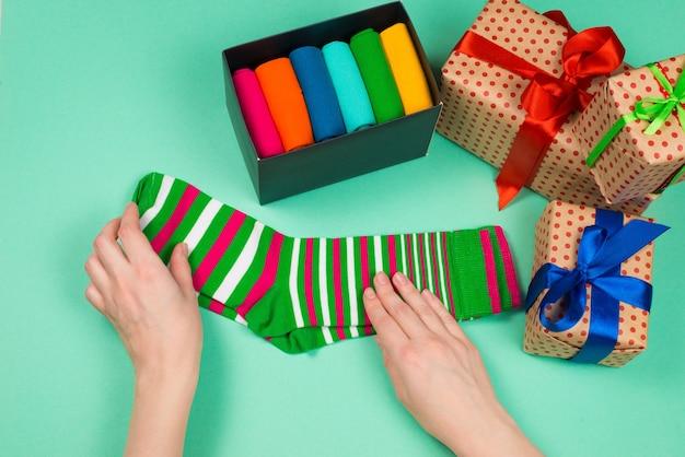 Kolorowa kolekcja bawełnianych skarpetek na prezent w rękach kobiety.