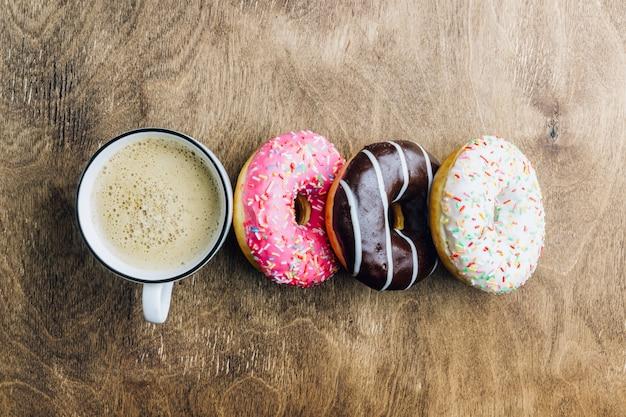 Kolorowa kompozycja śniadaniowa donuts z różnymi kolorami pączków i kawy