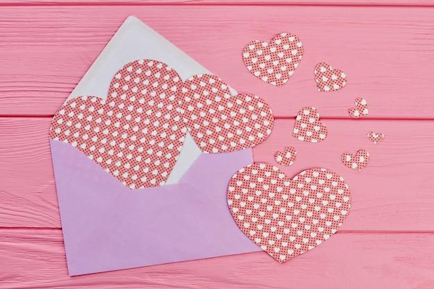 Kolorowa koperta z papierowymi serduszkami.