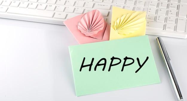 Kolorowa koperta z piórem na klawiaturze na białym tle z tekstem szczęśliwy