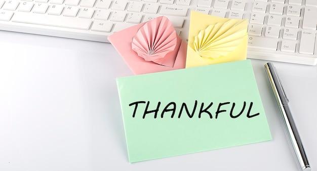 Kolorowa koperta z piórem na klawiaturze na białym tle z tekstem wdzięczny