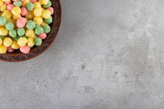 Kolorowa kulka kukurydzy w misce na marmurowym stole.