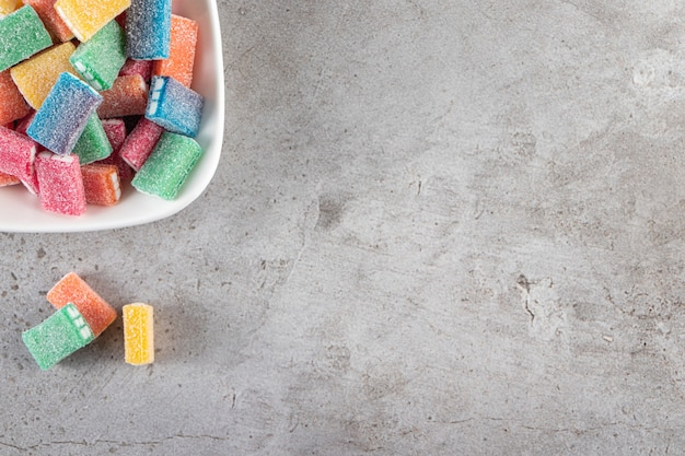 Kolorowa lukrecja w okrągłej białej misce umieszczonej na kamiennym stole.