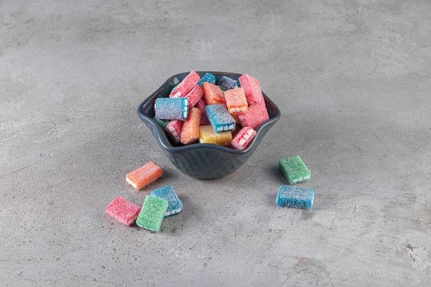 Kolorowa lukrecja w okrągłej czarnej misce umieszczonej na marmurowym tle.