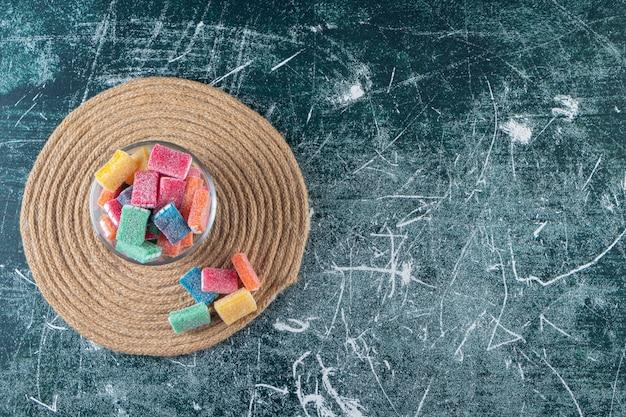 Kolorowa lukrecja w okrągłej szklanej misce umieszczonej na marmurowym stole.