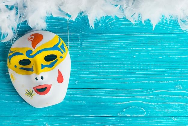 Kolorowa maska i białe pióra