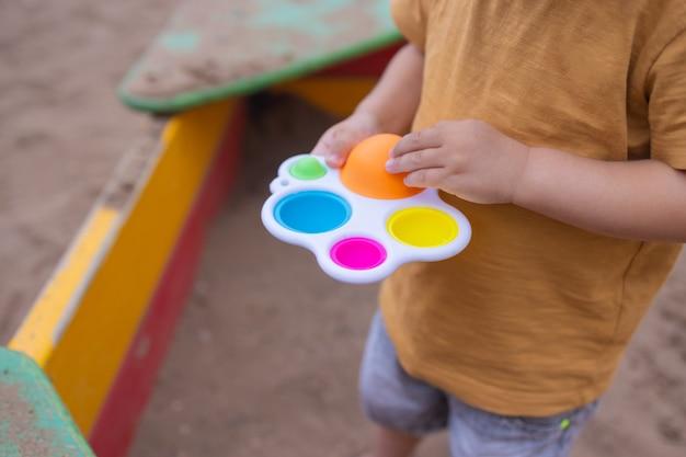 Kolorowa, modna antystresowa zabawka sensoryczna fidget push pop i prosty dołek w rękach dzieci, które dzieci dzielą się zabawkami i bawią się razem