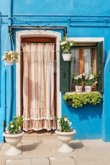 Kolorowa niebieska fasada domu z zasłoniętymi drzwiami, drewnianymi okiennicami na oknie i roślinami doniczkowymi na parapecie
