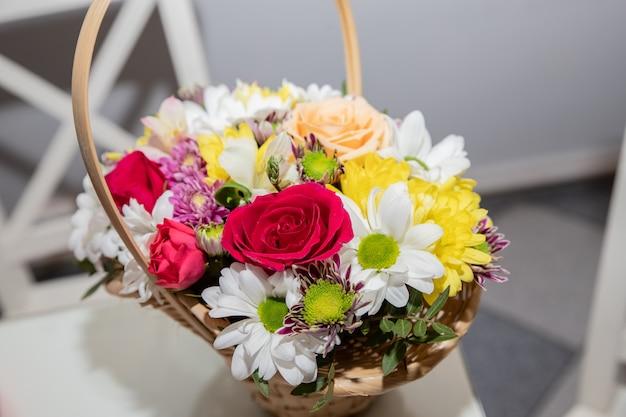 Kolorowa ornamentacyjna rozmaitość kwiaty w prezenta drewnianym koszu z różami, liściem i chryzantemą, stokrotki, selekcyjna ostrość. przygotowania kwiat. wiosenny bukiet na wakacje.