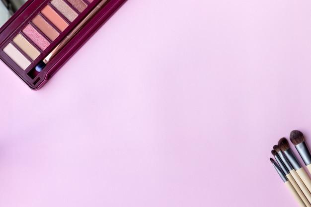 Kolorowa paleta cieni do powiek w różowej kolorystyce oraz zestaw pędzli do makijażu na różowym, liliowym tle papieru z miejscem na kopię. profesjonalna paleta kolorów do makijażu oczu z matowymi i połyskującymi cieniami