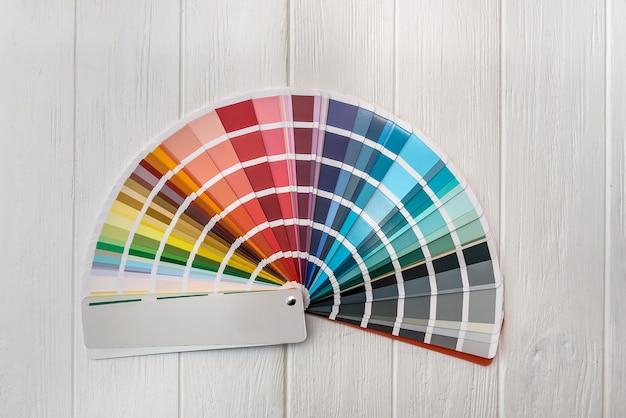 Kolorowa paleta do malowania ścian na drewnianym biurku