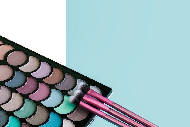 Kolorowa paleta makijażu z trzema różowymi pędzlami na niebieskim tle