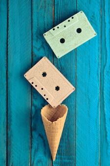 Kolorowa pastelowa kaseta magnetofonowa i pusty róg gofra na niebieskim drewnianym stole. widok z góry, minimalistyczny trend, kreatywny układ