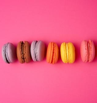 Kolorowa piec macarons migdałowa mąka na różowym tle