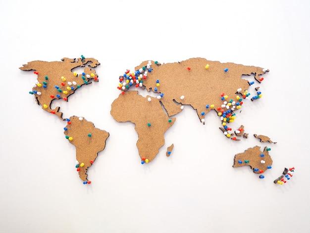 Kolorowa pinezka do oznaczania lokalizacji na drewnianej mapie świata na ścianie
